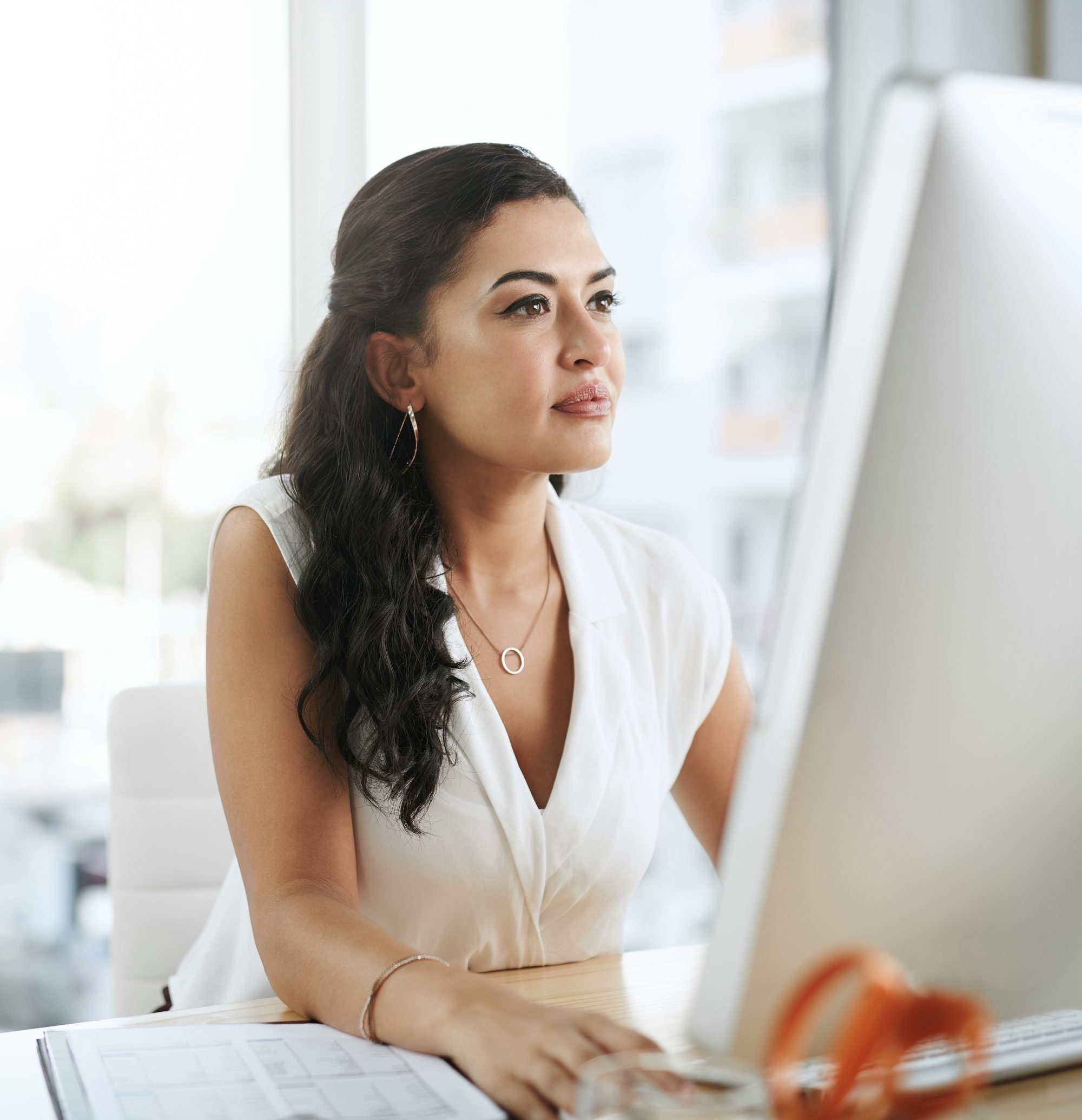 Shot of a young businesswoman using a computer at her desk in a modern office