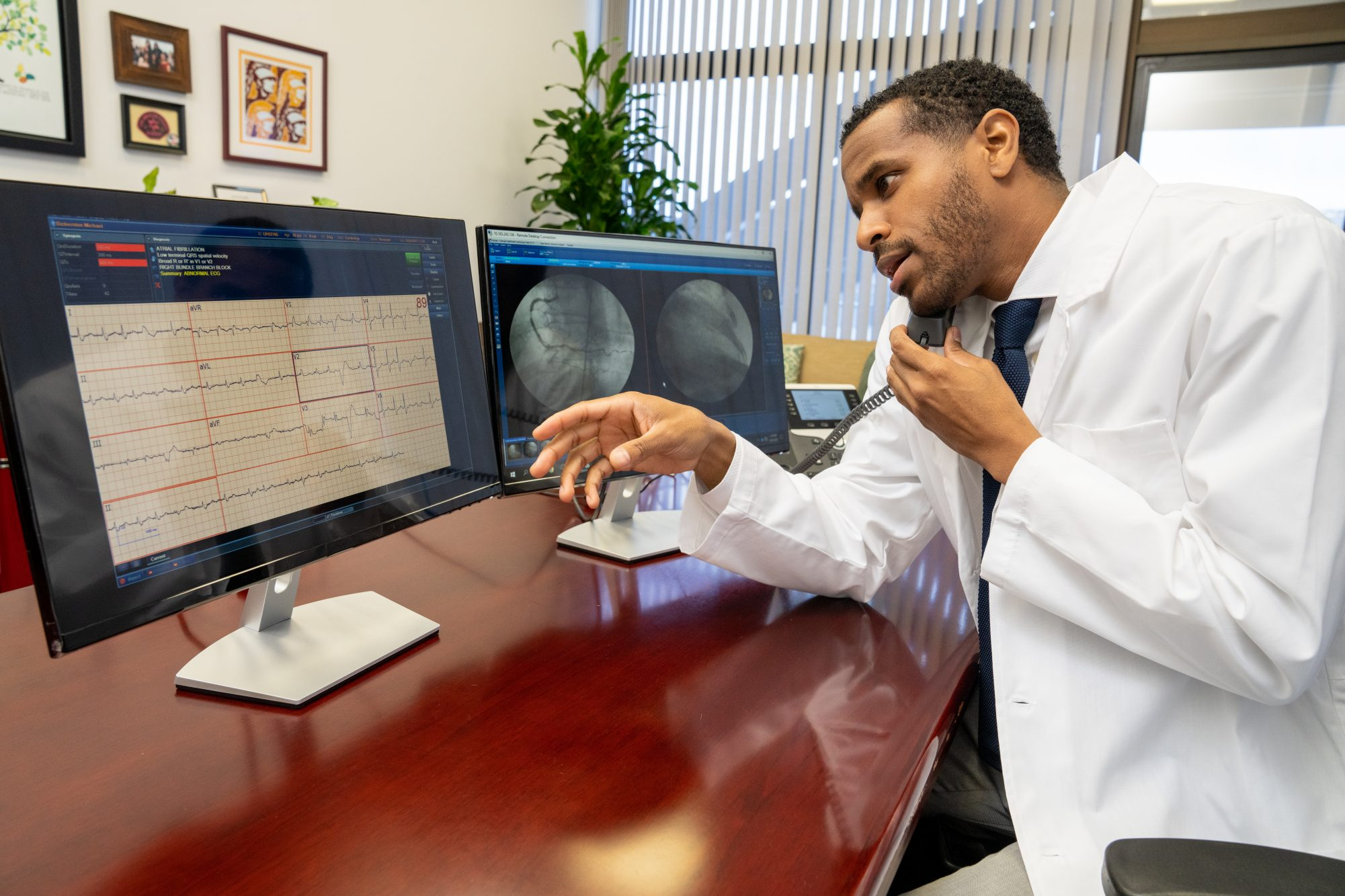 Cardiologist analyzing information on monitor while on phone