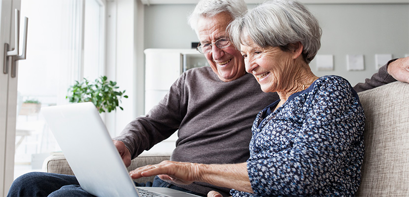 Happy senior couple looking at computer